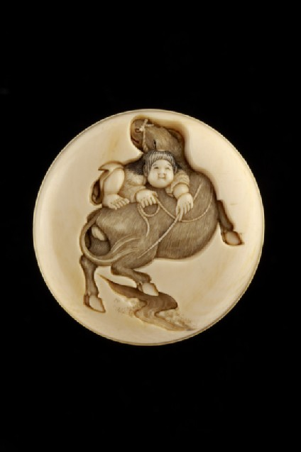 Manjū netsuke depicting an ox-herd trying to mount his ox