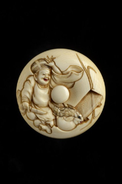 Manjū netsuke depicting a smiling priest about to prepare a puffer fish