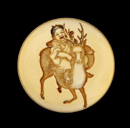 Manjū netsuke depicting a child riding a sacred deer