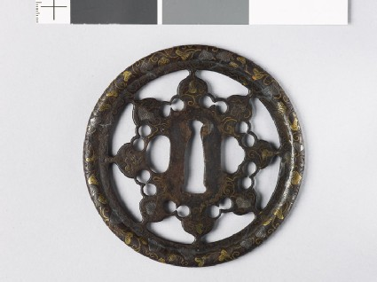 Round tsuba with karakusa, or scrolling plant pattern, interspersed with aoi, or wild ginger