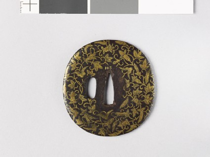 Lenticular tsuba with leaves and flowers