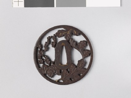 Round tsuba with chrysanthemum leaves and mon made from kiri, or paulownia leaves