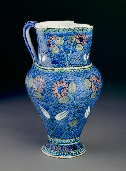 Jug with flowers against a fish-scale background