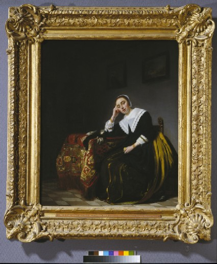 A Woman seated beside a Table