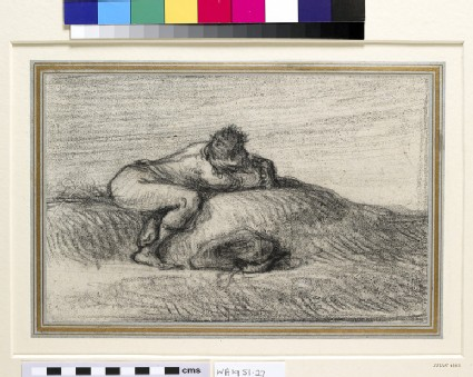 A man crouching on a hillock