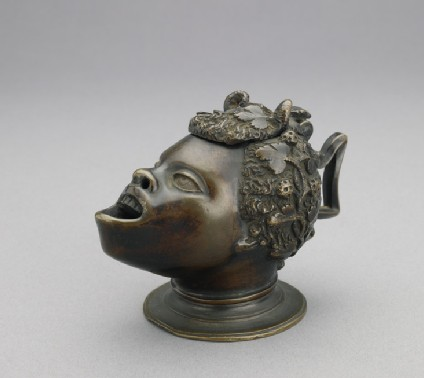 Oil lamp in the form of the head of a satyr with African features