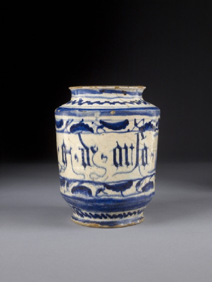 Albarello, or pharmacy jar, straight-sided, flanged at rim. Painted in blue with plant motifs and a scroll