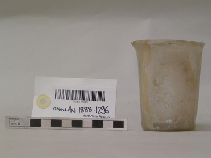 Cylindrical white glass beaker with indented decoration around the body