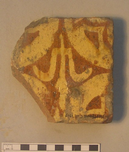 Tile with yellow on brown decoration