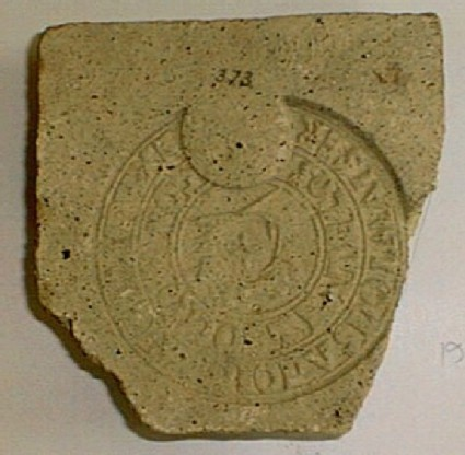 Brick stamped with Latin script, cross and wreath in central circle
