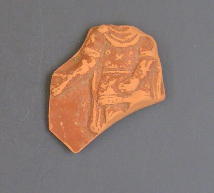 Fragment of a Samian (red ware) jar decorated in appliqué with a figure of a standing man in Phrygian dress