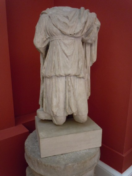 Statue of male torso of Cautes holding his torch up