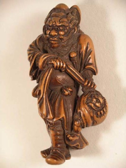 Netsuke in the form of Shōki holding a captured demon in a bag