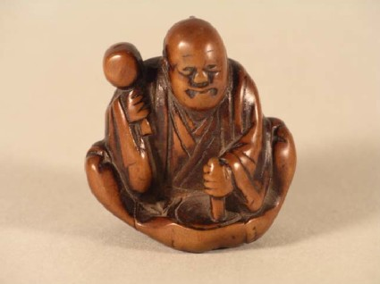 Netsuke in the form of a seated mask maker, working on a mask of Okame
