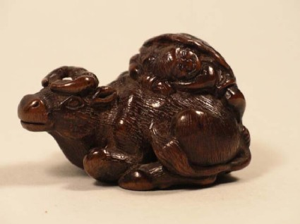 Netsuke in the form of an ox sitting down with a herdboy asleep on its back