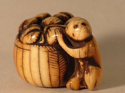 Netsuke in the form of a monkey stealing fish from a basket