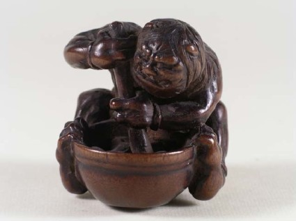 Netsuke in the form of an oni, or demon, mixing a potion in a pestle and mortar