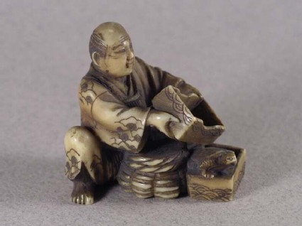 Netsuke in the form of a man releasing tortoise from a box