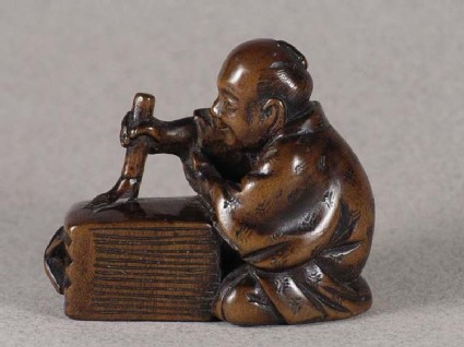 Netsuke in the form of a figure painting a ledger with a large brush