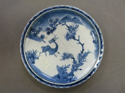 Dish with deer and maple leaves in a mountainous landscape