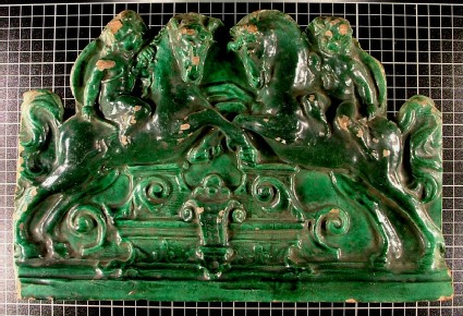 Moulded stove tile with two horses, ridden by putti over architectural feature