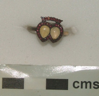 Gold betrothal ring, the bezel formed as two hearts surmounted by a coronet and set with a border of twenty-eight garnets crowned by seven jargoons
