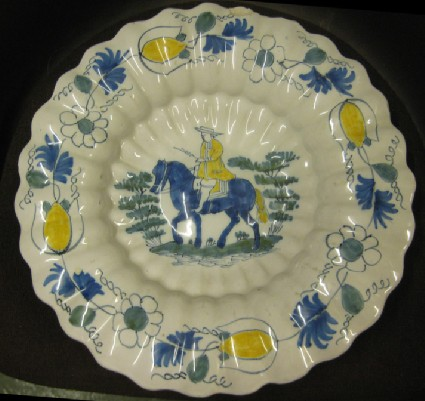 Lobed dish with horseman between trees in centre