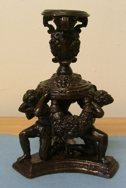 Vase candlestand supported by three kneeling putti