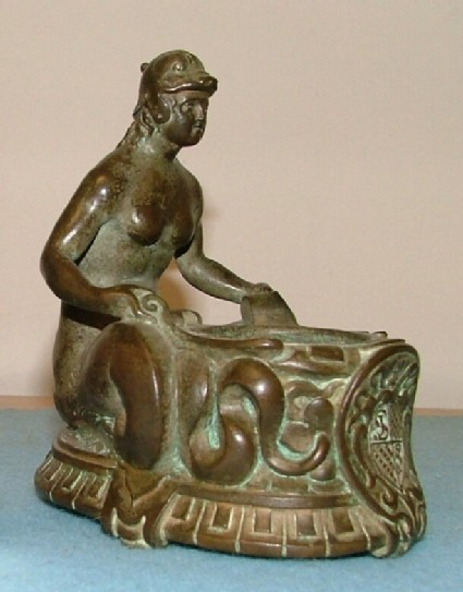 Inkstand in the form of a mermaid holding a receptacle for an inkwell