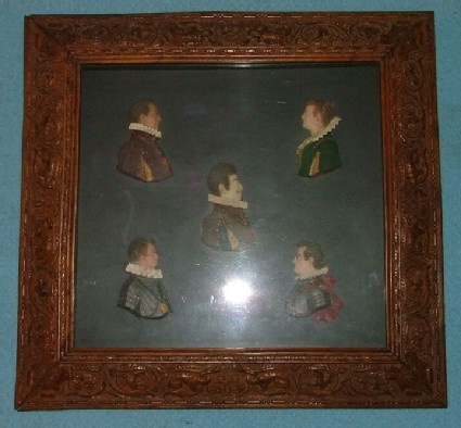 Five profile portrait busts in a carved frame
