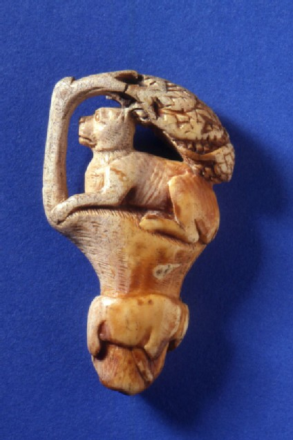 Roman ivory knife handle featuring a setting of a dog or large cat resting under a tree