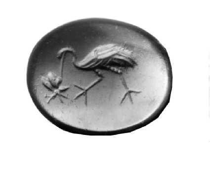 Red carnelian intaglio depicting a crane in profile picking on a butterfly or libel