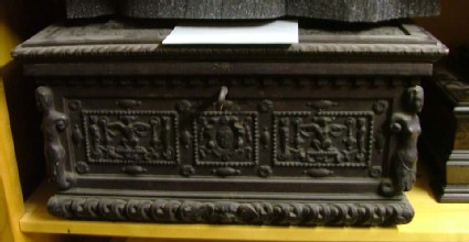 Casket with applied winged masks and sirens