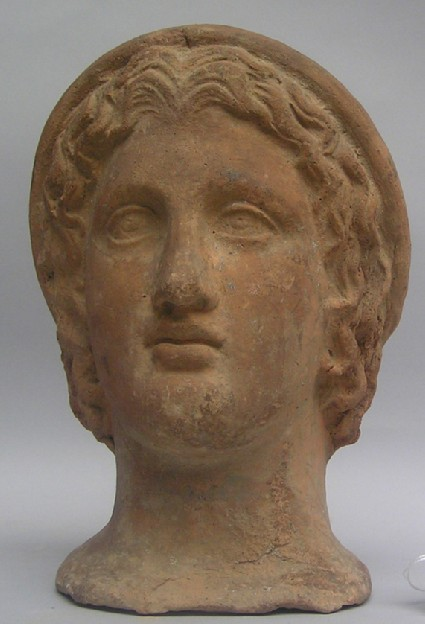 Terracotta head of youth wearing a cap