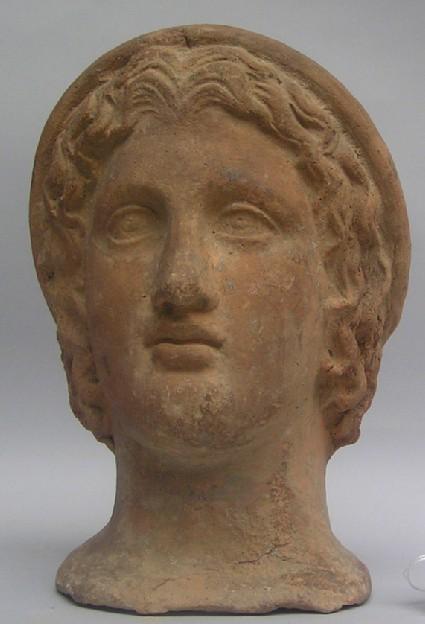 Terracotta head of youth wearing a cap