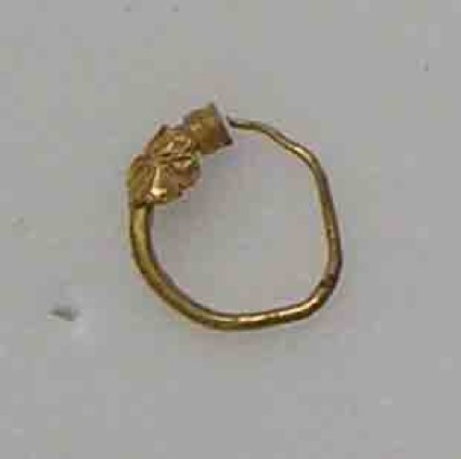 Tiny gold hoop earring terminating in small collar with a rosette ornament
