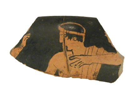 Attic red-figure pottery cup sherd possibly depicting a komos scene