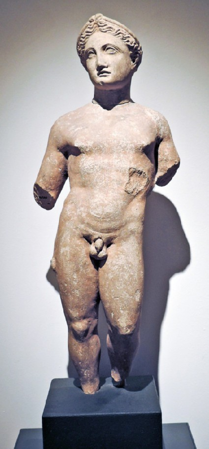 Limestone statue of a naked youth with braided hair around head and bun above forehead (head and torso originally separate)