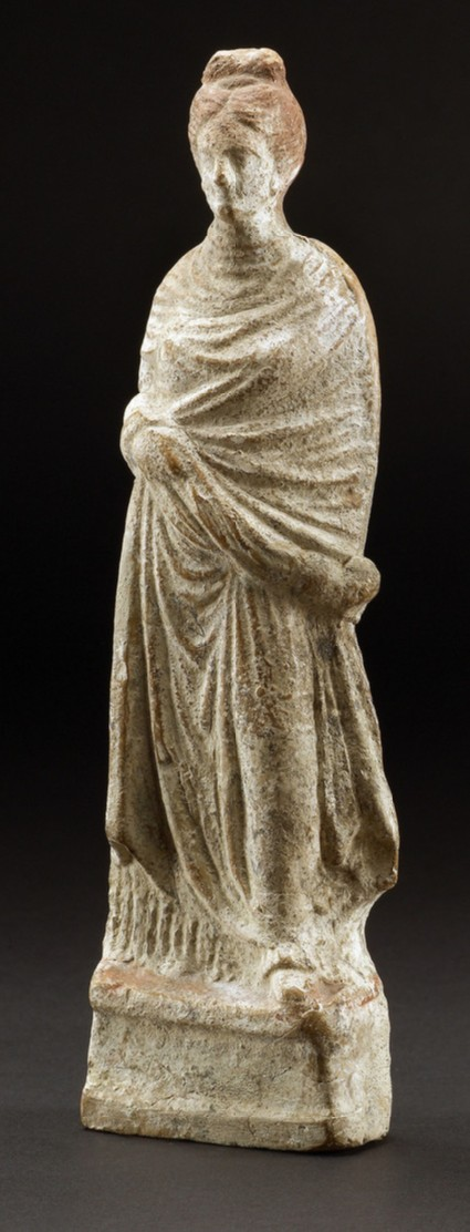 Terracotta figurine of a woman wrapped in her cloak with an Aphrodite-type hairstyle