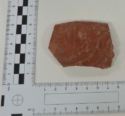 Sherd of Samian bowl, winding scroll with broad leaves, tendrils and flying bird