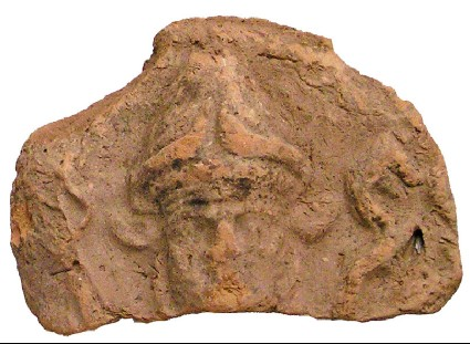 Fragment of a mould-made plaque showing the head and sceptre tops of an underworld deity