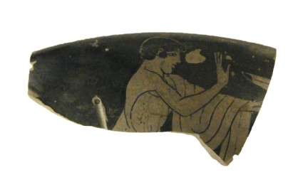 Attic red-figure pottery cup fragment depicting a symposiastic scene