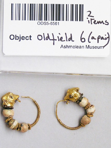 Pair of gold hoop earrings with bull-head terminals and threaded with glass beads on hoop