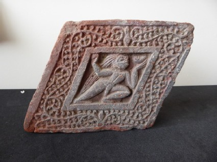 Diamond-shaped brick depicting an ascetic or yogi in relief