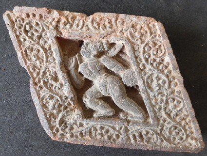 Diamond-shaped brick depicting an armed warrior in relief