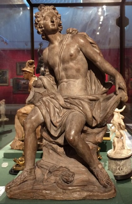 Apollo, seated holding his lyre, attentive to the Muses