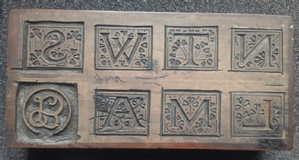 Woodblock for Initial letters N, T, W, S, L, M, A, mostly uncut, with SLB in circle