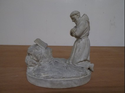 Statuette of St Francis, kneeling before a rock