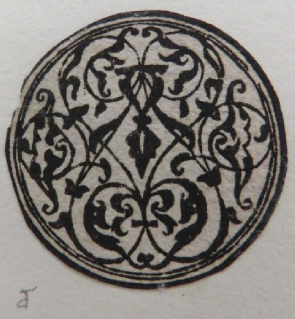 Small circular medallion with an arabesque crewelwork design in black with two concentric circles at border, from Douce Ornament Prints Album I