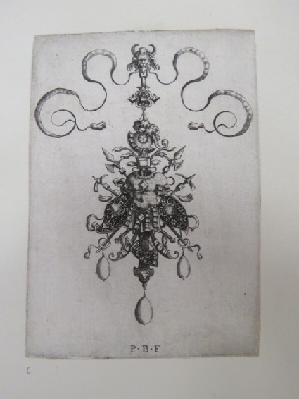 Pendant design with breastplate in centre surrounded by other trophies of shields, spears, and axes topped by a helmet, grotesque lion head at top, from Douce Ornament Prints Album I